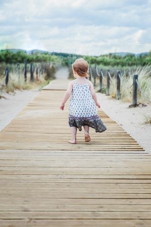 little girl running along a wooden walkway on the beach in summer
