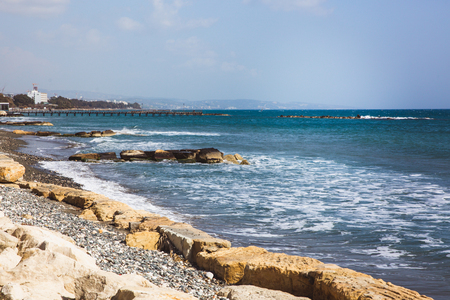 Empty stone beach on Limassol seafront on a sunny spring day. Waves at sea