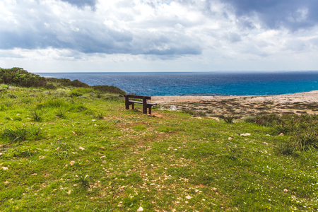 Bench stands on the seashore. Beautiful valley by the sea. Seascape in Cyprus Ayia Napa. Cape Greco peninsula, national forest park