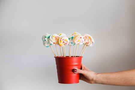 Hand holding colorful meringue lollipops on a stick in red pail, white background. Vintage pastel colored French meringues.