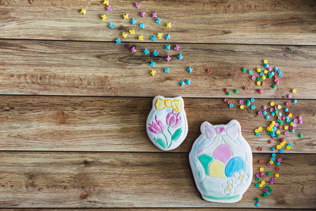 Sweets, pastry for Easter table. Easter handpainted gingerbread with colored sprinkles on wooden background. top view copy space