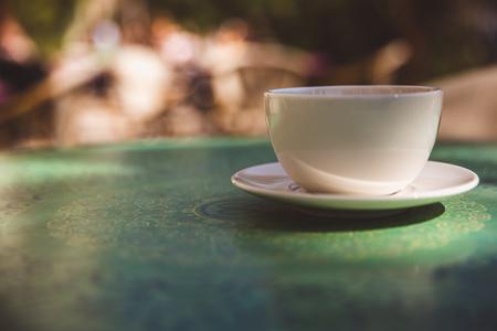Kaffeetasse auf tadellosem grünem Tischhintergrund im Freien - weiche Lichteffektartbilder. Nahaufnahme, Modell