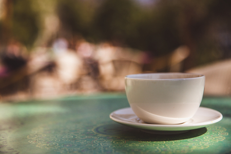Coffee mug on mint green table outdoor background - soft light effect style pictures. Close-up, mock-up