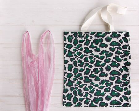 Eco Shopping Bag with trendy leopard pattern print against a plastic bag on white wooden background, Flat Lay. Save planet earth