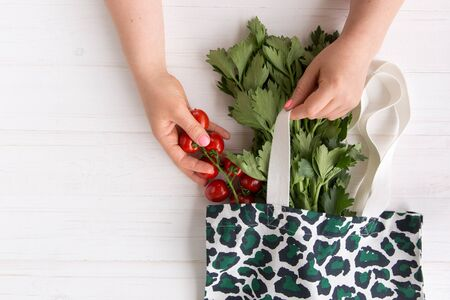 Hands of a woman take out fresh organic tomatoes from Eco Shopping Bag with trendy leopard pattern print on wooden background, Flat Lay. Top View