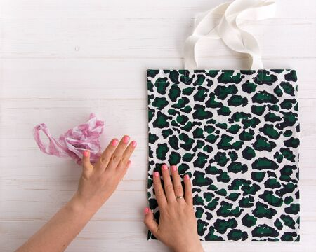 Womans hands choose eco shopping bag with trendy leopard pattern print against a plastic bag on white wooden background, Flat Lay. Save planet earth
