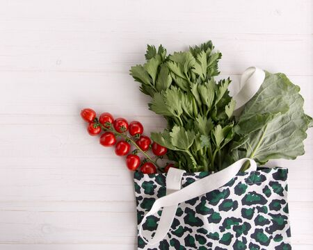 Eco Shopping Bag in trendy leopard pattern print with fresh organic vegetables and salad on white wooden background, Flat Lay