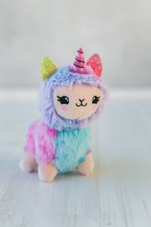 Colored plush llama unicorn on white wooden background Stock fotó