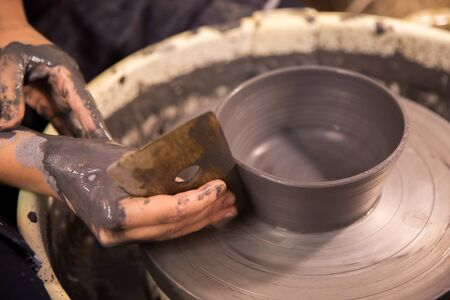 Womens hands at work on a potters wheel with black clay