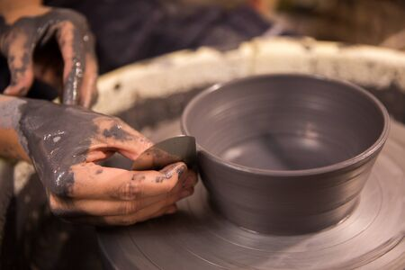 Womens hands at work on a potters wheel with black clay Imagens