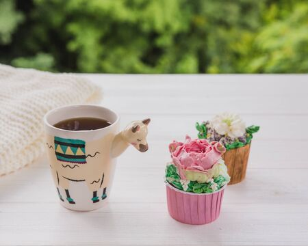 Beautiful llama shaped trendy cup with hot drink and two cupcakes on white wooden table with bright greens background