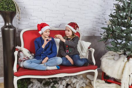 Happy cute little kids in Santa hats eating delicious cookies at home Banque d'images - 129473073