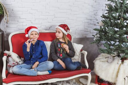 Happy cute little kids in Santa hats eating delicious cookies at home