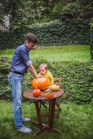 Happy halloween. Father and daughter carving pumpkin for Halloween outside and pulls seeds and fibrous material from a pumpkin before carving for Halloween. Happy family