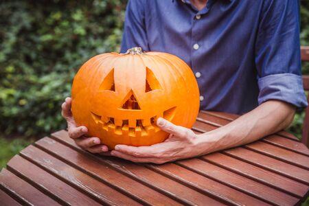 Hombre de camisa azul con gran calabaza delante de su cara. Feliz Halloween