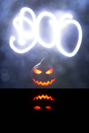 Halloween pumpkins smile and scrary eyes for party night. Close up view of scary Halloween pumpkin with eyes glowing inside at black background. The word Boo is drawn by a light beam Reklamní fotografie