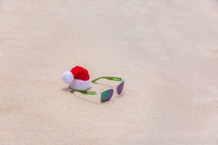Santa Christmas hat with sunglasses in sand on a tropical beach. Holiday tropic summer concept