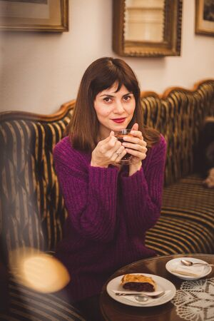 Cozy lifestyle shot of gorgeous European women wearing trendy sweater enjoying aroma and flavor of coffee while relaxing in old cozy cafe Banque d'images - 132185989