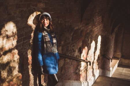 Young A tourist woman in trendy blue coat on the wall of the Fishermans Bastion of Budas Castle in Budapest in winter Banque d'images - 132185988