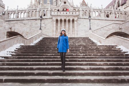 A tourist woman in trendy blue coat stands on the stairs of the Fishermans Bastion in the Castle in Budapest Banco de Imagens