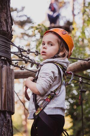 Kleines süßes Mädchen, das im Hochseilgarten klettert und das Abenteuer genießt