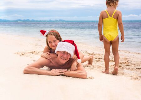 Young friendly family father and two dauthers are happy in summer Christmas on beach. Christmas concept Stock Photo