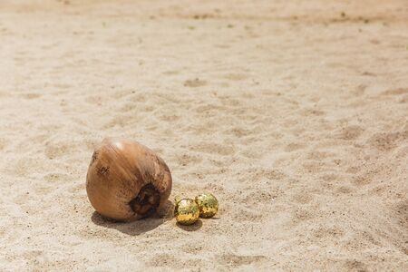 Christmas gold balls in the sand near coconut Banque d'images - 132186062
