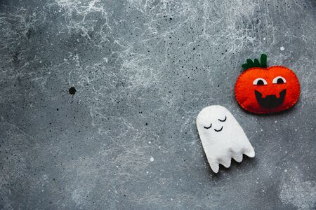 Flat lay Halloween background with decorative pumpkin and ghost on a grey backdrop. Copy space for text Banque d'images - 132186070