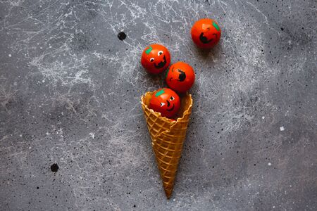 Waffle cone is filled with candies Halloween pumpkins on the grey background Banque d'images - 132186098