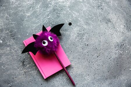 Trendy purple bat pencil and pink notebook for notes on grey background. Halloween still life. Flat lay