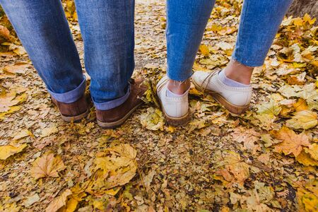 Womans and mans boots on dry fall leaves in the nature park outdoor and autumn season Banque d'images - 132434442