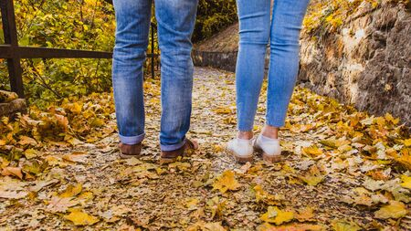 Womans and mans boots on dry fall leaves in the nature park outdoor and autumn season Banque d'images - 132434245