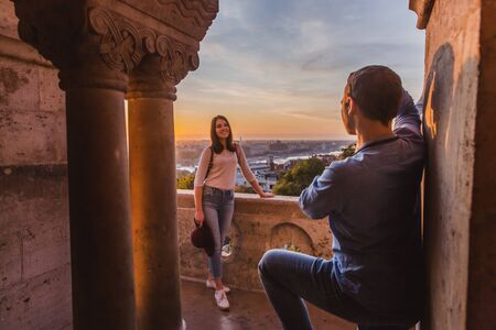 Young couple take pictures of each other on the view point from Fisherman Bastion in Budapest on sunrise. Reklamní fotografie