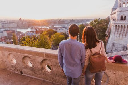 Young couple enjoy the view from the point from Fisherman Bastion in Budapest, Hungary during sunrise. Banque d'images - 132596156