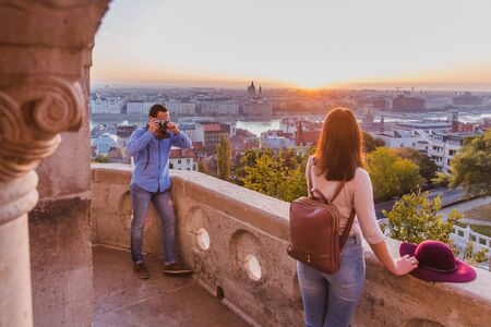 Young couple take pictures of each other on the view point from Fisherman Bastion in Budapest, Hungary on sunrise.