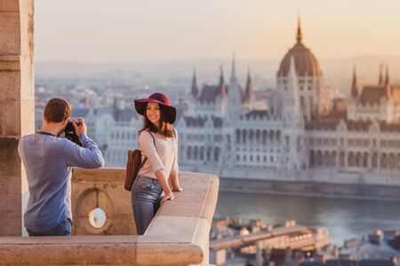 Young couple take pictures of each other on the view point from Fisherman Bastion in Budapest on sunrise. Banque d'images - 133088792