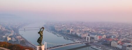 Aerial view to the Statue of Liberty with Elisabeth Bridge and River Danube taken from Gellert Hill on sunrise in fog in Budapest, Hungary. Banque d'images - 132653118