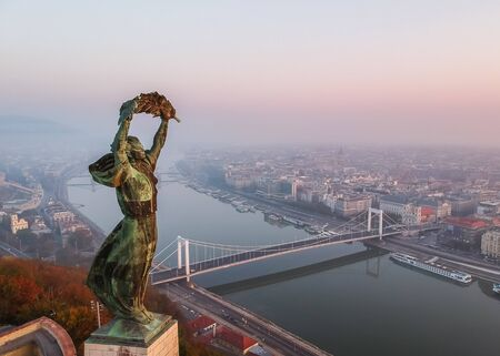 Aerial view to the Statue of Liberty with Elisabeth Bridge and River Danube taken from Gellert Hill on sunrise in fog in Budapest, Hungary. Banque d'images - 132653525