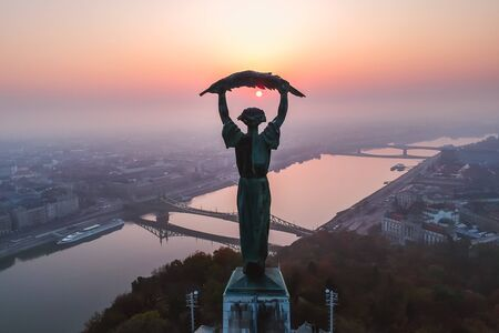 Aerial view to the Statue of Liberty with Liberty Bridge and River Danube at background taken from Gellert Hill on sunrise in fog in Budapest, Hungary Banco de Imagens