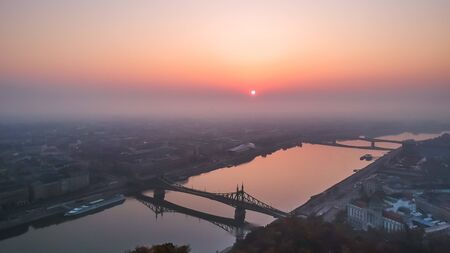 Aerial view to the Liberty Bridge and River Danube taken from Gellert Hill on sunrise in fog in Budapest, Hungary Banque d'images - 132654935