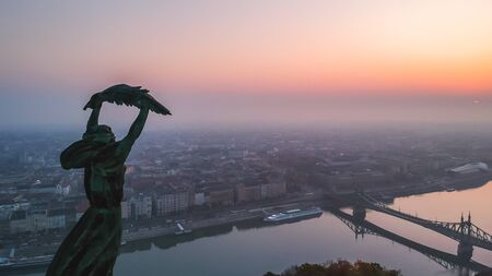 Aerial view to the Statue of Liberty with Liberty Bridge and River Danube at background taken from Gellert Hill on sunrise in fog in Budapest, Hungary Banque d'images - 132656169