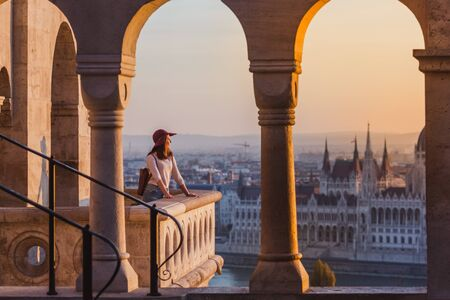 A happy young woman enjoying her trip to the Castle of Budapest in Hungary on the view point from Fisherman Bastion on sunrise. Banque d'images - 132723700