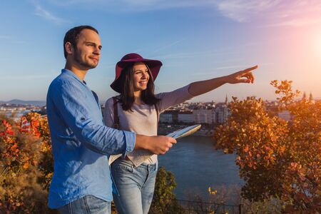 Young couple searching right direction on map from the point from Gellert Hill in Budapest during sunrise