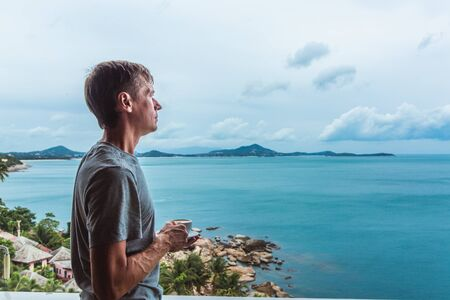 Young man standing near the window with coffee cup and enjoying a view to the ocean on the tropical island Фото со стока - 134487127