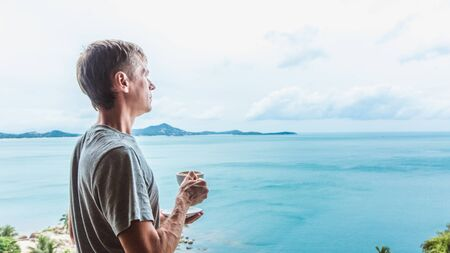 Young man standing near the window with coffee cup and enjoying a view to the ocean on the tropical island Banque d'images - 132812132