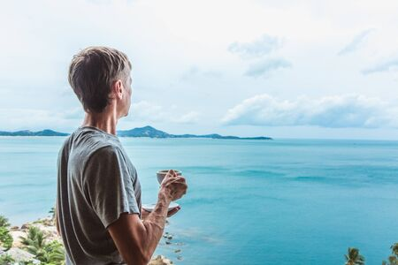 Young man standing near the window with coffee cup and enjoying a view to the ocean on the tropical island Banque d'images - 132813275