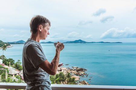 Young man standing near the window with coffee cup and enjoying a view to the ocean on the tropical island Banque d'images - 132815522
