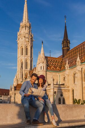 Young couple searching right direction on map from the point from Fisherman Bastion in Budapest with Matthias Church on background Banque d'images - 133243505