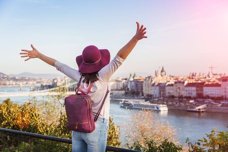 A happy young woman enjoying her trip to Budapest, Hungary from the point from Gellert Hill during sunrise in autumn during sunrise. Banque d'images - 133244533