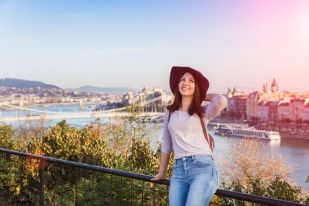 A happy young woman enjoying her trip to Budapest, Hungary from the point from Gellert Hill during sunrise in autumn during sunrise. Banque d'images - 133249937